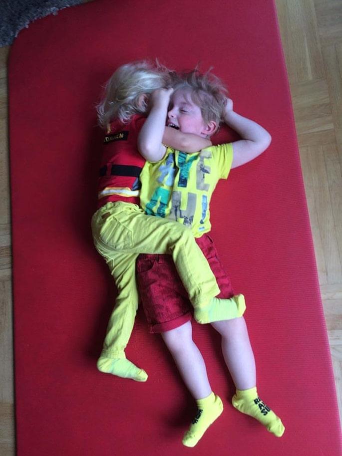 Elton & Noomi kramas på en röd matta på golvet