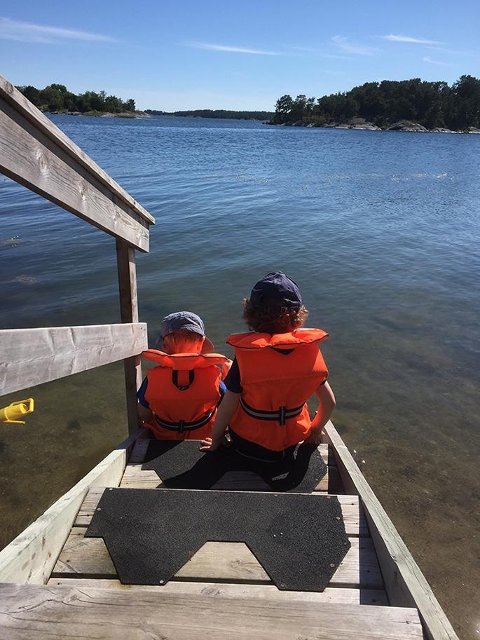 Lillebror och Storebror sitter på en trappa ned mot havet iklädda flytvästar