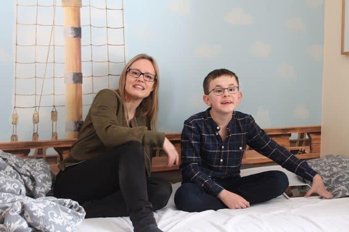 Susanne och Gustav sitter i Gustavs säng och ser glada ut