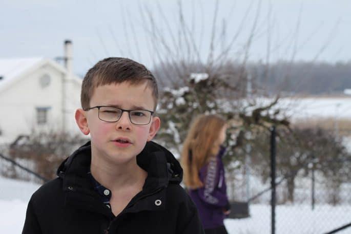 Gustav i förgrunden och Freja suddigt i bakgrunden i en snöig utomhusmiljö