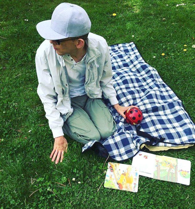 Zandras bror på en picnickfilt på en grön gräsmatta