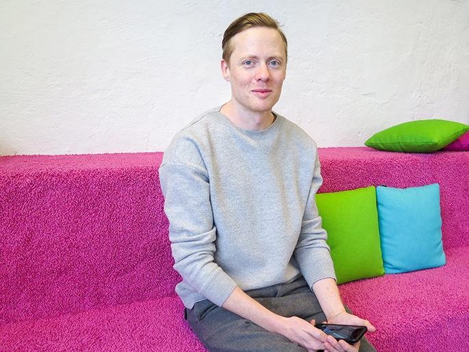 Johan Wendt sitter på en rosa soffa