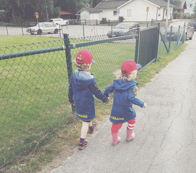 Sebastian och Max går hand i hand utomhus i matchande jackor och kepsar