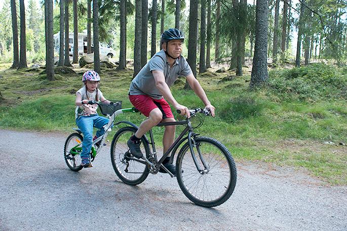 Malin och Matti cyklar på en påhängscykel på en camping