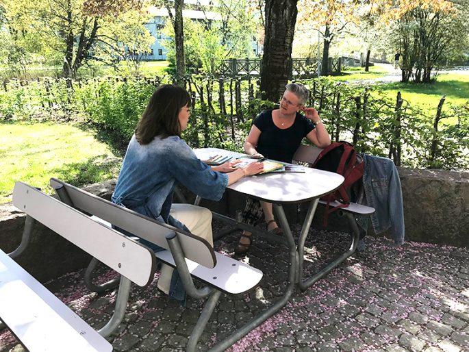 Ann-Charlotte och Jenny sitter tillsammans vid ett bord utomhus
