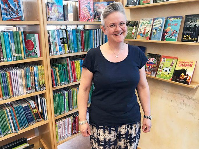 Ann-Charlotte står framför massor av böcker på bibliotek Fyren i Kungsbacka