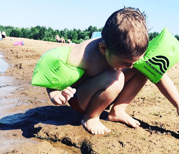 Alen sitter på en strand med gröna armpuffar och plockar något från sanden