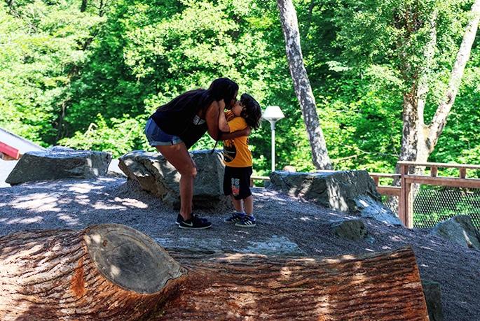 Linn och Tristan står på en sten och pussar varandra på munnen