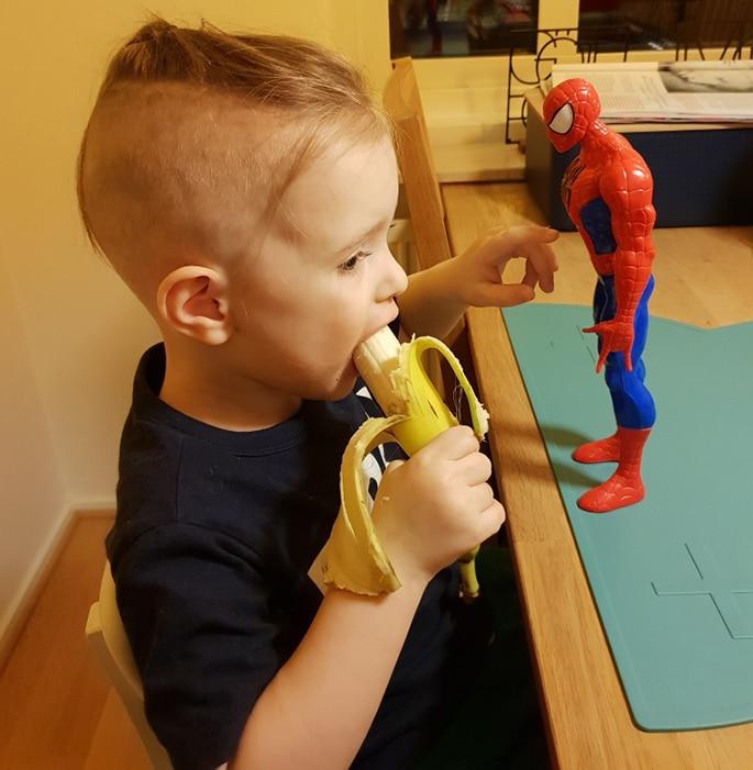 Oscar sitter vid ett bord och äter en banan med en spindelmannen-figur framför sig