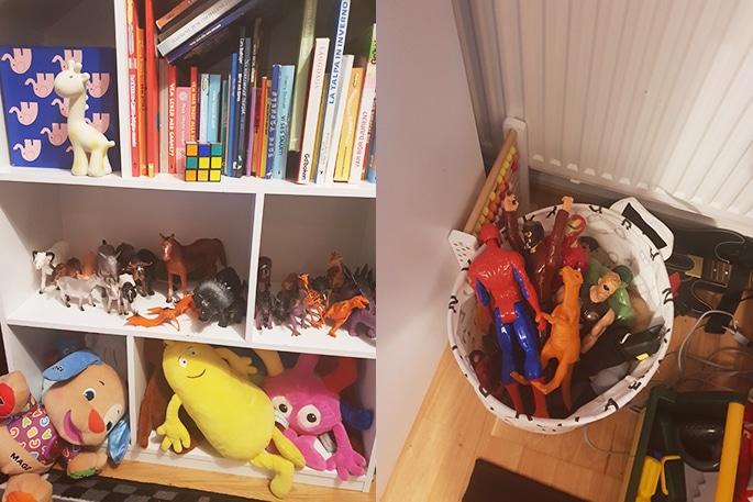 En bokhylla med böcker och gosedjur samt en korg på golvet med färgglada figurer