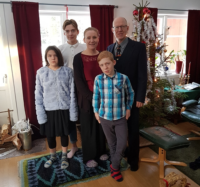 Otto and his family standing in front of a Christmas tree
