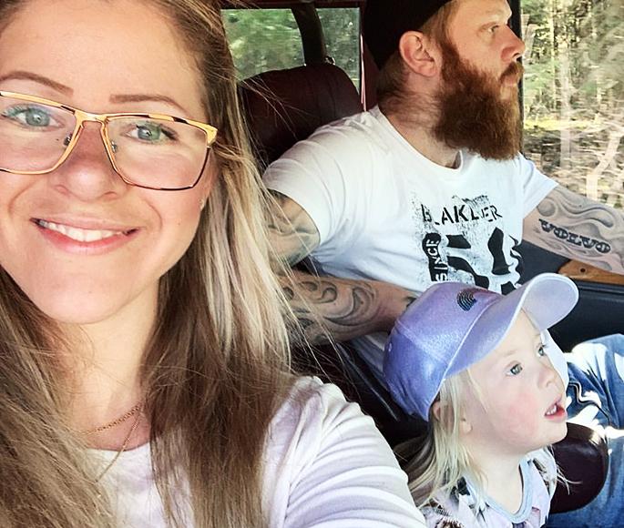 Juni sitter i ett fordon tillsammans med mamma och pappa. Mamma Josefine tittar in i kameran.