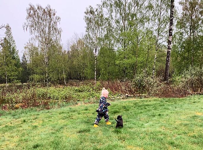 Juni springer ute på en gräsmatta med hunden Uno