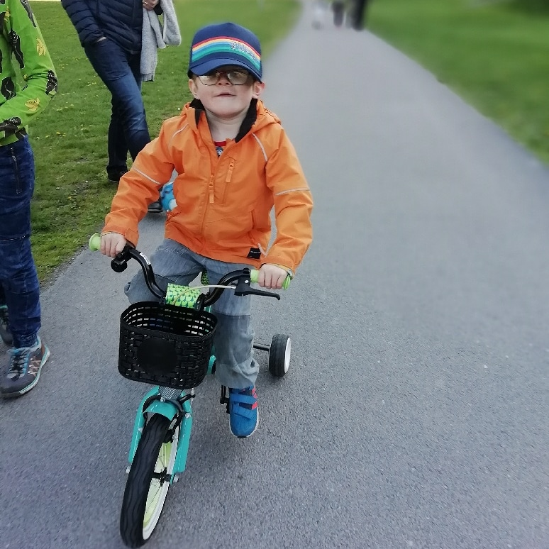Sigge wearing an orange jacket, riding a blue bike