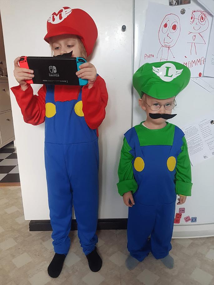 Sixten och Knut står på ett golv. Sixten är utklädd till Super Mario och håller i ett Nintendo Switch som han tittar på. Knut är utklädd till Luigi och tittar in i kameran.
