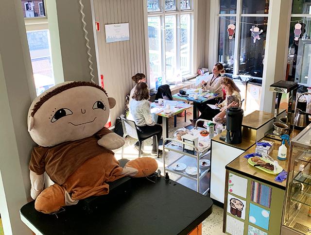 En docka föreställande Alfons sitter i förgrunden. I bakgrunden ser man fem personer runt ett bord.